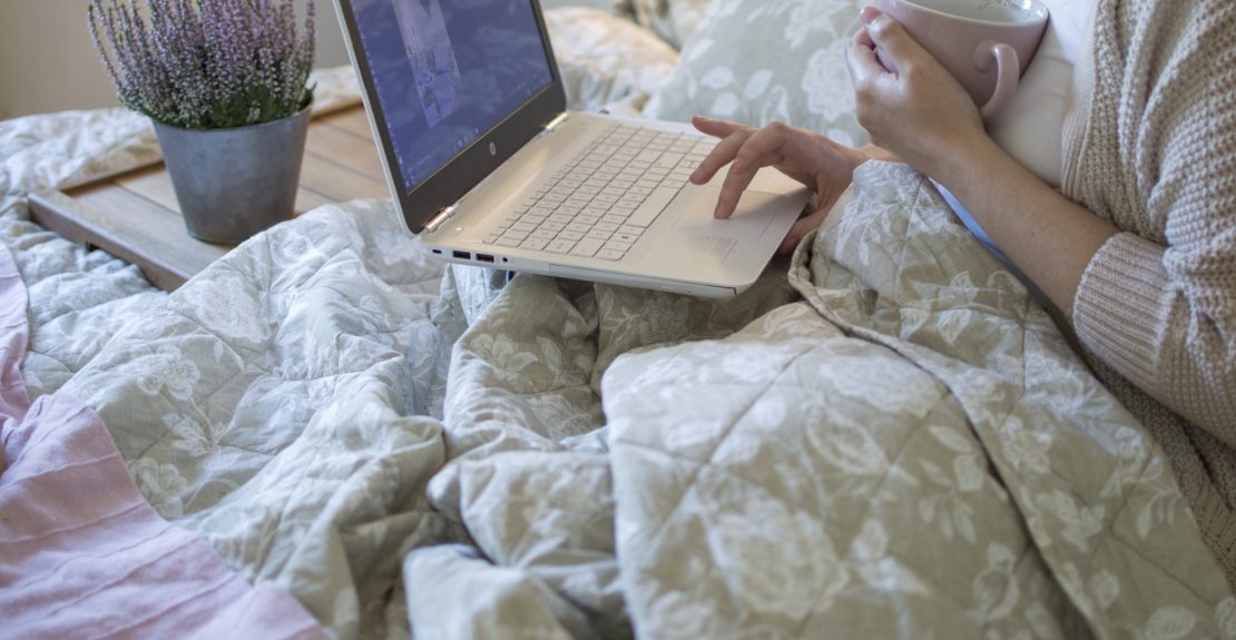 a-woman-sitting-in-a-feminine-bedroom-as-she-drinks-tea-and-uses-her-laptop-computer_t20_g82dVz